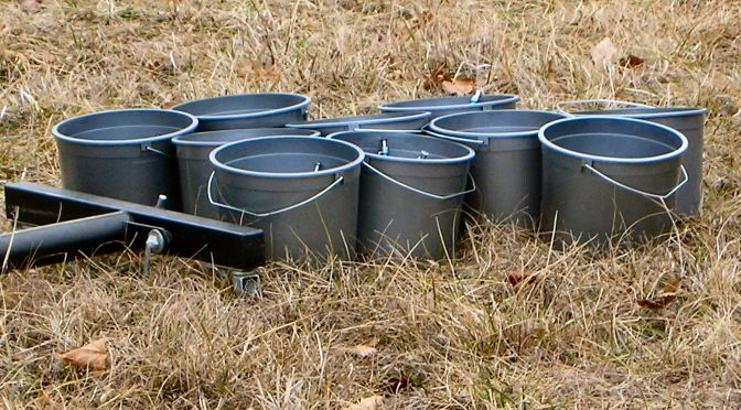 Image of several gray buckets sitting in the grass.