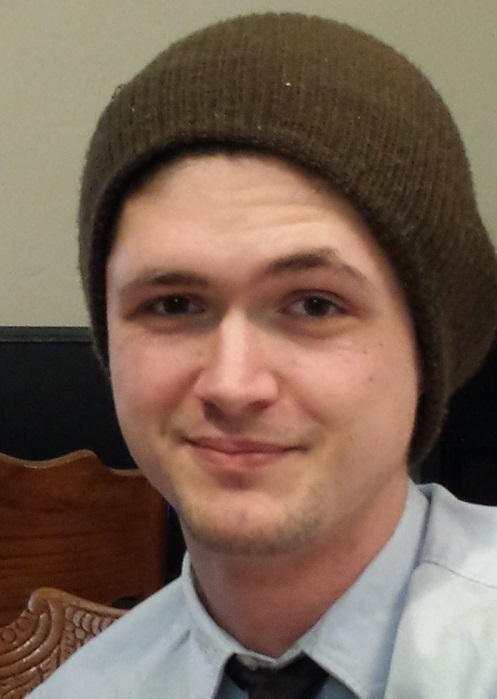 Picture of a man in a shirt and tie, with a beanie hat on his head