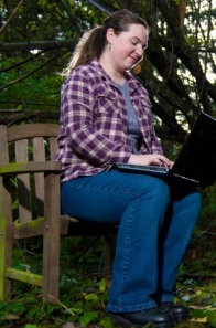 Photograph of Kate Ringland sitting on bench with laptop