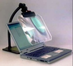 A photo of a computer screen magnification lens positioned in front of a laptop computer screen, magnifying it.