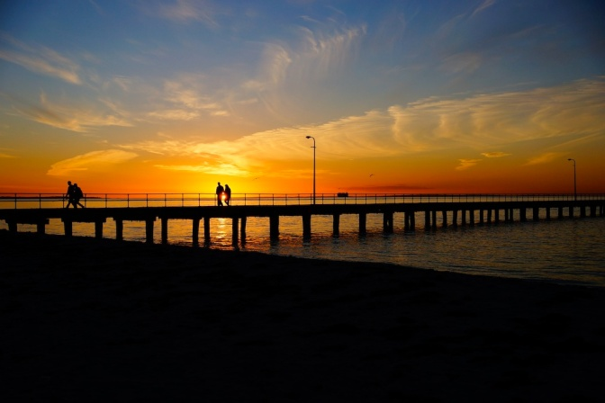 Image of a jetty with a sunset behind it.