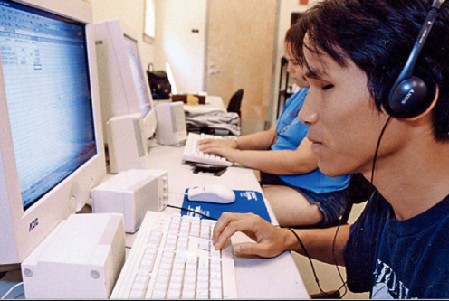 A photo of a visually impaired person using a screen reader computer program to read website content