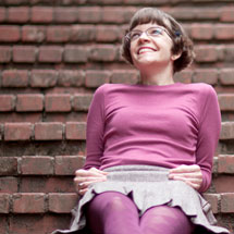 A photograph of Tina Granzo sitting on red brick stairs outside.
