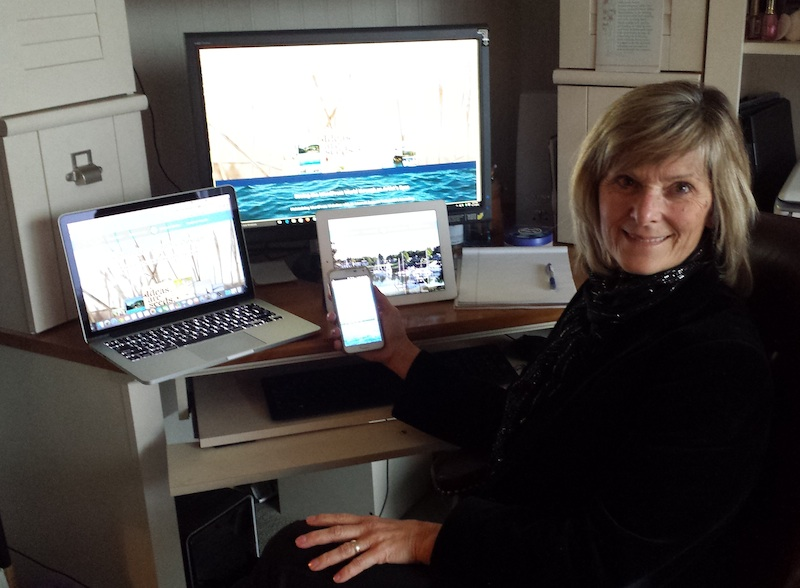 Photo of Cheri Calvert with a Windows desktop, Apple Notebook, Tablet, and Android phone.